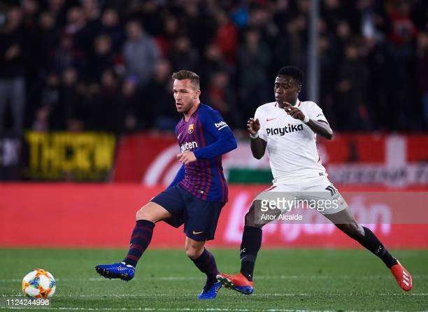 Arthur of FC Barcelona competes for the ball with Quincy Promes of Sevilla FC during the Copa del Quarter Final match between Sevilla FC and FC...
