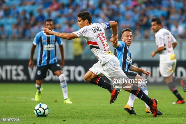 Arthur of Gremio battles for the ball against Hernanes of Sao Paulo during the match between Gremio and Sao Paulo as part of the Brasileirao Series A...