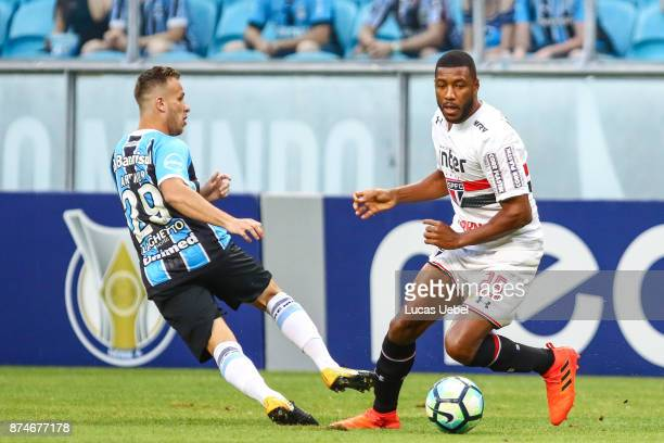 Arthur of Gremio battles for the ball against Jucilei of Sao Paulo during the match between Gremio and Sao Paulo as part of the Brasileirao Series A...
