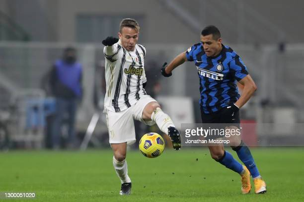 Arthur of Juventus controls the ball as Alexis Sanchez of Internazionale closes in during the Coppa Italia semi-final match between FC Internazionale...