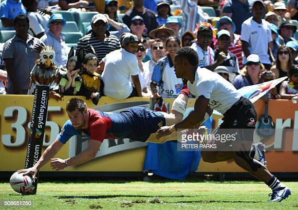 Arthur Retiere of France scores a try as Amenoni Nasilasila of Fiji runs in in their Pool C match in the Sydney Sevens rugby Union tournament in...