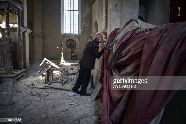 Arthur Sahakyan prays inside the damaged Ghazanchetsots Cathedral in the historic city of Shusha, some 15 kilometers from the disputed...
