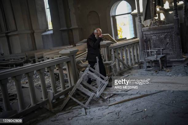 Arthur Sahakyan walks inside the damaged Ghazanchetsots Cathedral in the historic city of Shusha, some 15 kilometers from the disputed...