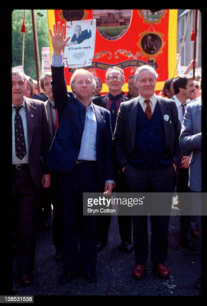 Arthur Scargill president of the National Union of Mineworkers center left waves to miners and their supporters as he walks with Tony Benn a Labour...
