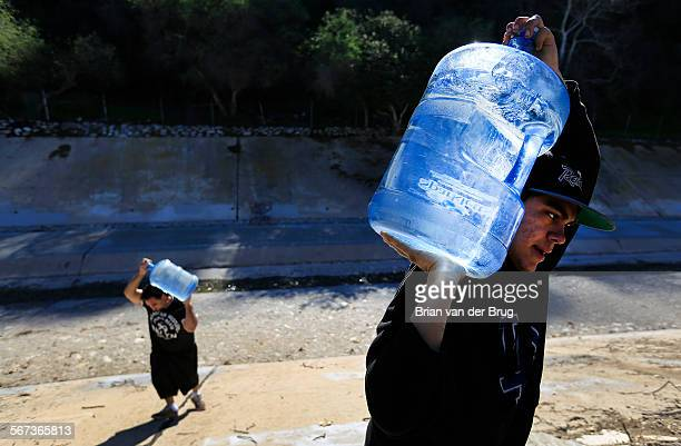 January 17, 2015: Arthur Valenzuela right, and Miguel Hernandez left, carry water up out of the Arroyo Seco to their tent homes along the Pasadena...