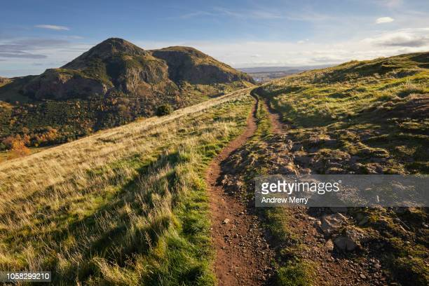 arthur's seat peak, summit, walking path on salisbury crags holyrood park, edinburgh - hill stock pictures, royalty-free photos & images