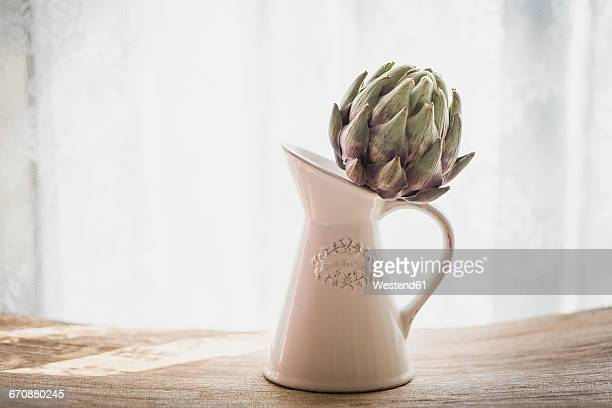Artichoke in jug, kitchen knife