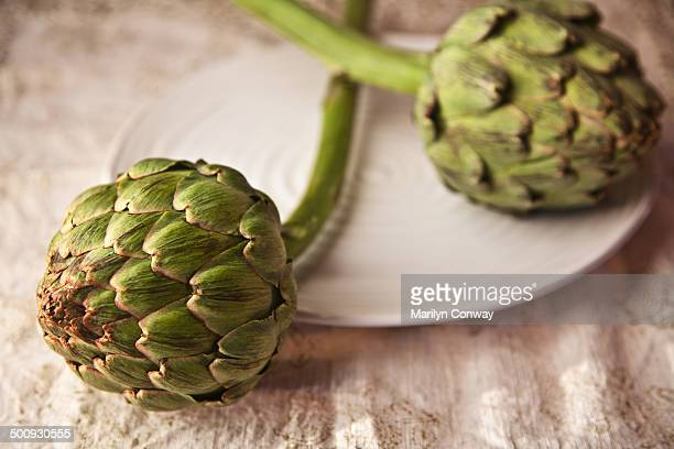 Artichokes on plate on table