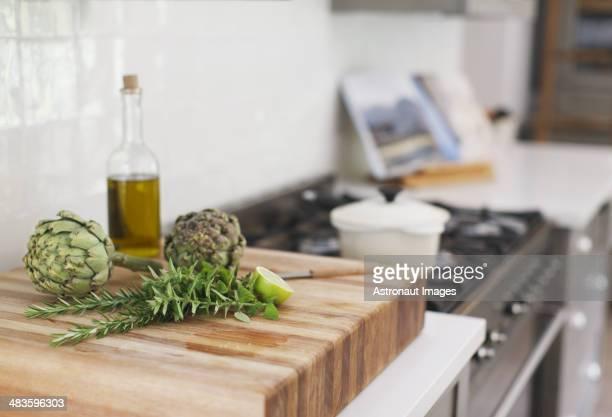 Artischocken, Rosmarin, Olivenöl und Limette auf Schneidebrett