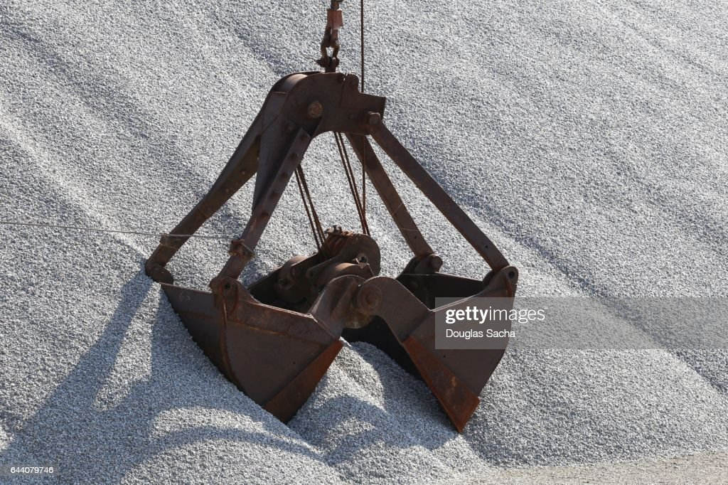 Articulated Clamshell Bucket grabs a load of stone : Stock Photo