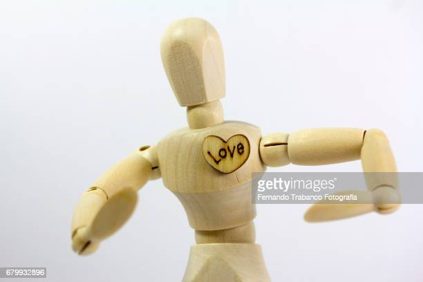 Articulated doll in love with a heart written love