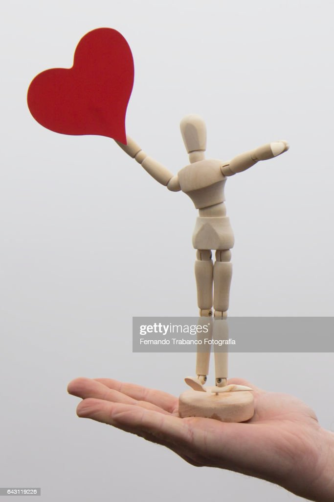 Articulated doll with a red heart over human hand : Stock Photo