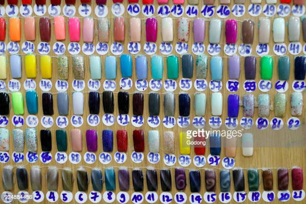 Artificial acrylic nails painted on display in nail salon Ho Chi Minh City Vietnam
