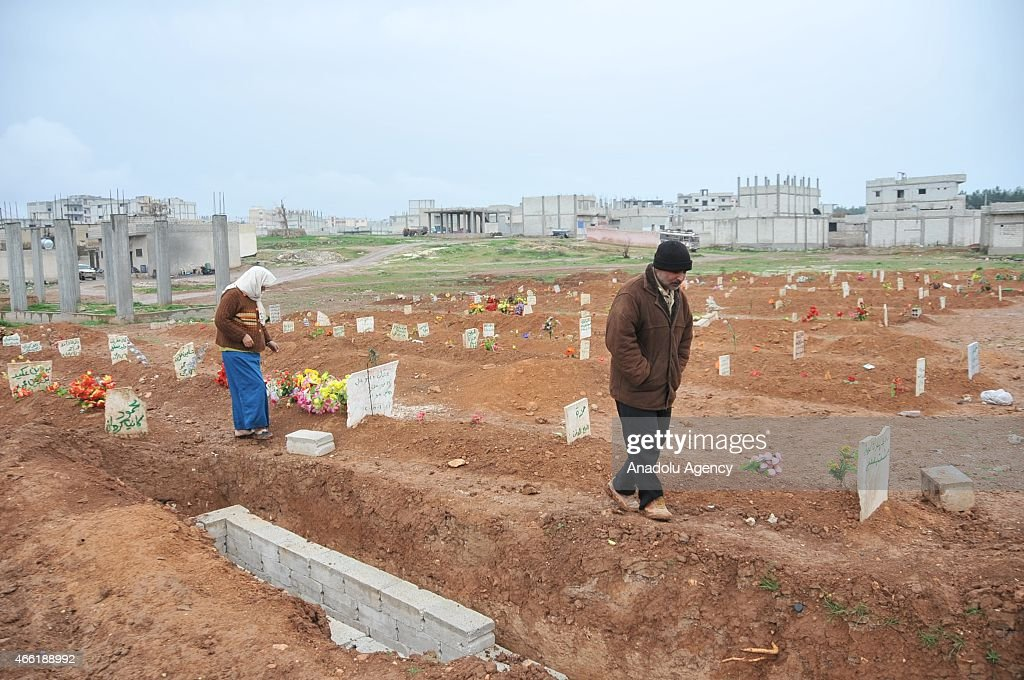 Artificial flowers are seen on the graves of Syrians who lost their lives during clashes in Kobani, Syria on March 12, 2015. Following around 4 months of clashes between DAESH (Islamic State of Iraq and the Levant) and Kurdish groups, a temporary medical centre has been opened in Kobani for patients there.