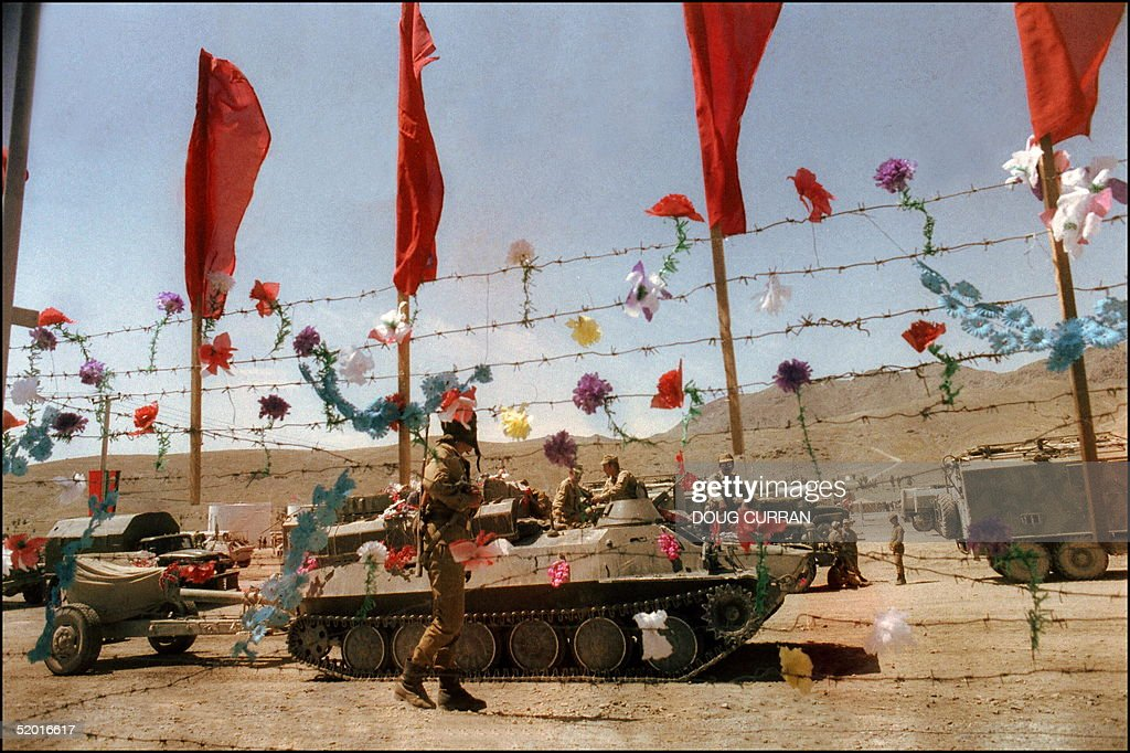 Artificial flowers decorate barbed wire fence as Soviet Army troops stop in Kabul 16 May 1988 prior to their withdrawal from Afghanistan. The Soviet Union invaded Afghanistan in December 1979 to shore up the pro-Soviet regime in Kabul and maintained more than 100,000 troops in the country until completing their phased withdrawal in 1989.