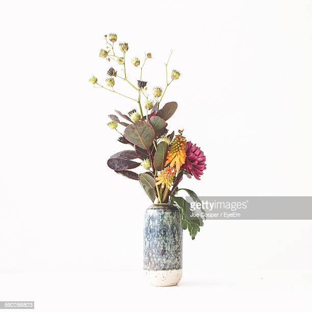 Artificial Flowers In Vase Against White Background