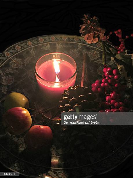 Artificial Fruits With Lit Tea Light Candle In Plate