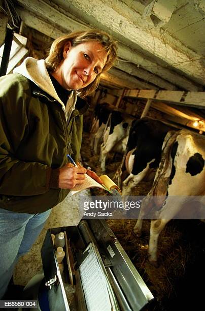 Artificial insemination technician taking notes in dairy barn