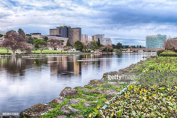 artificial lake by buildings in eur district against cloudy sky - eur rome stock pictures, royalty-free photos & images