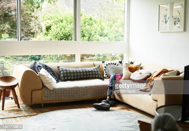 artificial leg leaning against sofa in sitting room - leaning disability stock pictures, royalty-free photos & images