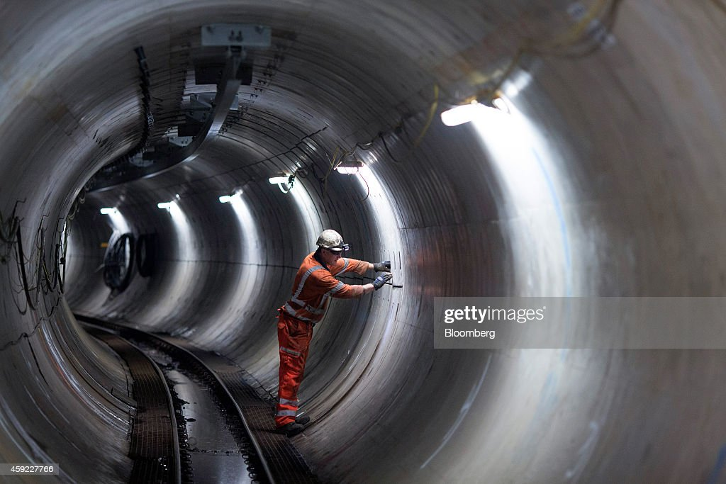 Artificial light illuminates a worker as he inspects a section of tunnel, during the construction of the National Grid Plc's London power-tunnels project, taking place underground near the Wandsworth area of London, U.K., on Monday, Sept. 29, 2014. National Grid Plc's 1 billion-pound power-tunnels project in London is 5 percent under budget and ahead of schedule, National Grid Chief Executive Officer Steve Holliday said. Photographer: Jason Alden/Bloomberg via Getty Images