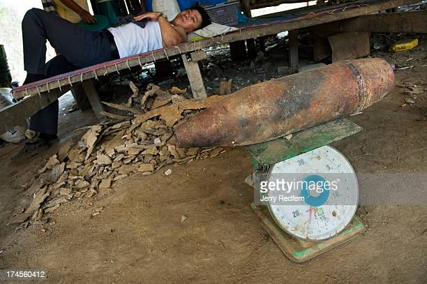 KG artillery shell is weighed for scrap in a Vietnamese trader's hut in Etoum In the background a man rests above a scrap pile containing bomb...