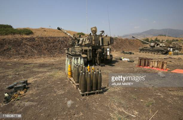 Artillery shells are lined up beside Israeli self-propelled artillery guns, near the Lebanese border on the outskirts of the northern Israeli town of...
