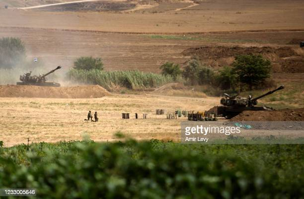 Artillery unit soldiers kneel after hearing a siren warning of rocket fire from the Gaza Strip as an artillery unit fires back on May 20, 2021 in...