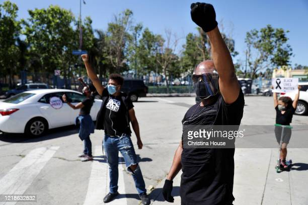 Artis Rutledge right and Daryl Tillis at left watch as a procession departs Leimert Park for downtown Los Angeles for a memorial service to honor...