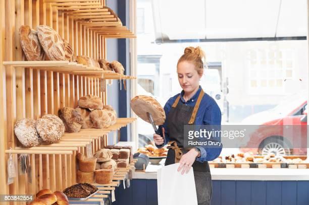 Artisan baker putting bread loaf in to bag