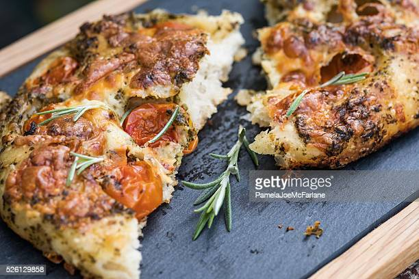 artisan focaccia bread pizza with cherry tomatoes, pesto, rosemary - artisanal food and drink stock pictures, royalty-free photos & images