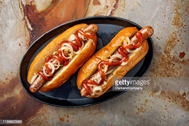 artisan hot dogs in a brioche bun with onions and ketchup. - brioche stock pictures, royalty-free photos & images