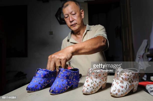 Artisan making shoes for bound feet Binding the foot of young girls was a tradition originated in the high classes of Chinese in order to keep the...