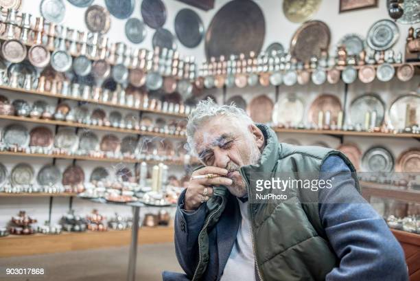 Artisan metal worker smokes in his shop Old Town Sarajevo Bosnia and Hercegovina on January 9 2018