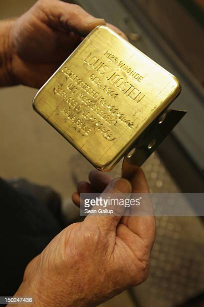 Artisan Michael Friedrichs-Friedlaender examines the text he just inscribed into a Stolperstein, which is a concrete cobblestone afixed with a brass...