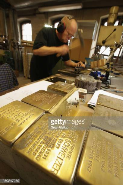 Artisan Michael Friedrichs-Friedlaender hammers inscriptions into the brass plaques of Stolpersteine, which are concrete cobblestones afixed with a...