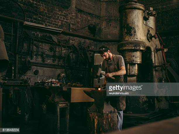 Artisan working iron in blacksmith's workshop