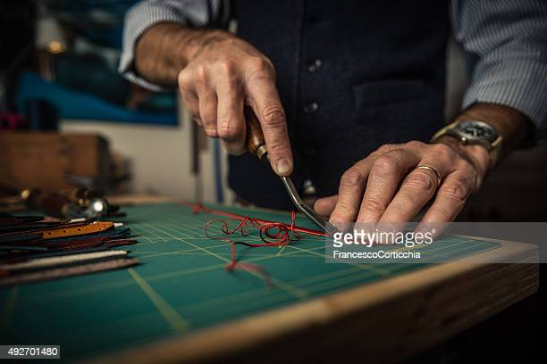 artisan working with leather - needle plant part stock photos and pictures