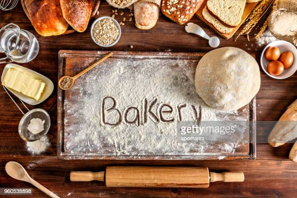 Artisanal bakery:  Bakery sign on cutting board. Fresh mixed Bun, rolls and ingredients