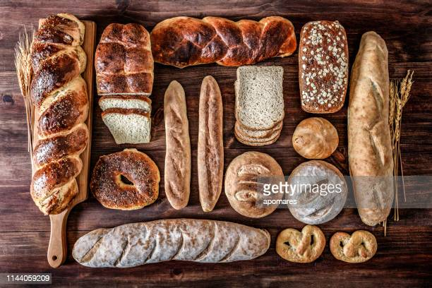 artisanal bakery:  fresh mixed bun, rolls and ingredients in a rustic kitchen - gluten free bread stock pictures, royalty-free photos & images