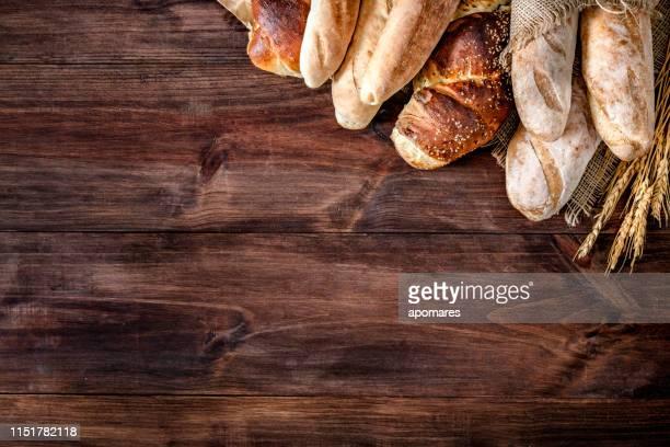 ambachtelijke bakkerij: vers gemengd broodje, broodjes en ingrediënten maken van een frame met kopieerruimte - brood stockfoto's en -beelden