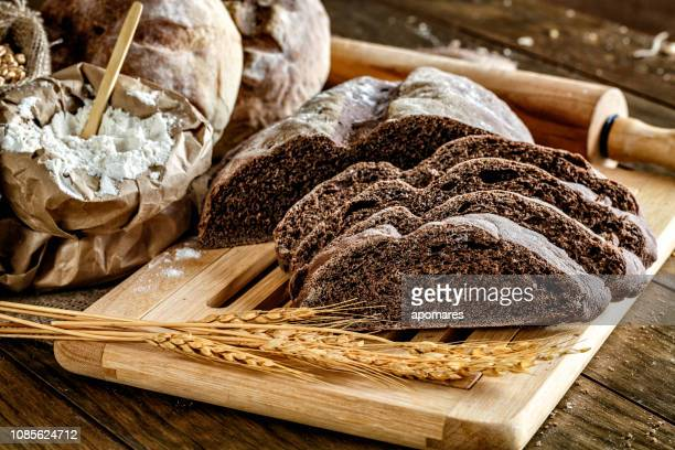 panificio artigianale: pagnotta di pane a lievitazione naturale e prodotti bun - pane integrale foto e immagini stock