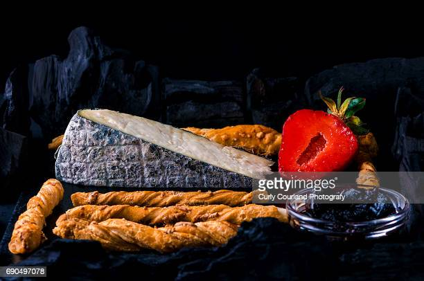 Artisanal cheese from cow milk with a covering of fine powdered charcoal served with puff pastry parmesan twists, strawberry and quince jam surrounded with charcoal