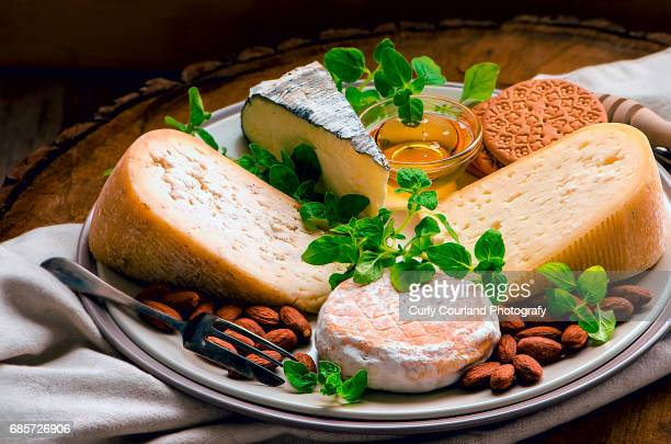 Artisanal cheese plate with honey, almonds, cookies and oregano