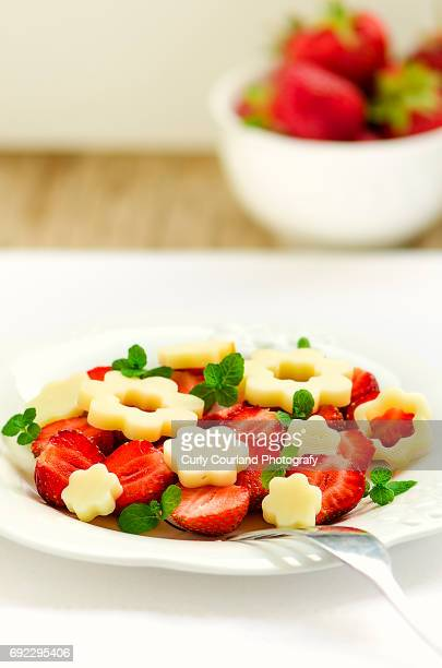 Artisanal cow milk flower shaped cheese with strawberries and mint