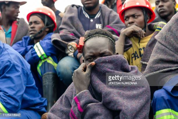 TOPSHOT Artisanal miners watch an ongoing rescue and recovery operation at the flooded Cricket gold mine near Kadoma Zimbabwe on February 17 2019...