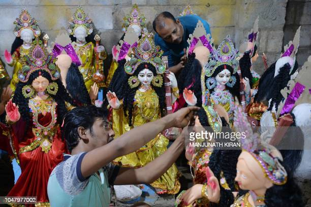 Artisans give finishing touches to clay idols of Hindu Goddess Durga at a workshop on the eve of Navarathri festivals during the Dasara celebrations...