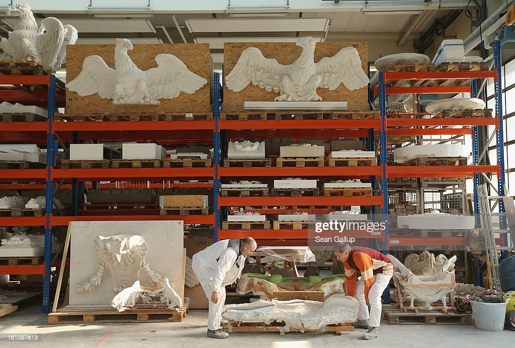Artisans move a silicon mould as plaster cast facade elements lie stored on shelves behind at the Schlossbauhuette studio where a team of sculptors is creating decorative elements for the facade of the Berliner Schloss city palace on February 12, 2013 in Berlin, Germany. The Berliner Schloss was the residence of the Prussian Kaiser and was among the major architectural landmarks of Berlin until it was heavily damaged by Allied bombing in 1945. The communist authorities of East Berlin demolished the building in the 1950s, and today's Berlin government is pursuing an ambitious project to rebuild the palace according to a design by Italian architect Franco Stella, which will recreate the facade of the building but with a modern interior at a cost of approximately EUR 590 million. The Humboldt Forum, the foundation leading the project, has given the Schlossbauhuette sculptors the formidable task of recreating the hundreds of architectural elements that decorated the facade, and though some original pieces were saved, more often the sculptors have only old black and white photos as reference.