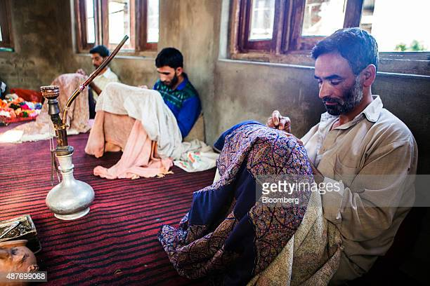 Artisans needleembroider cotton into pashmina sozni shawls at a home in Budgam district Jammu and Kashmir India on Tuesday Aug 25 2015 Pashmina goats...