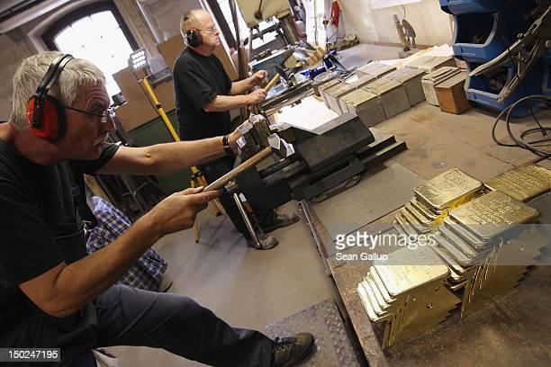 Artisans Rainer Schuette and Michael Friedrichs-Friedlaender prepare the brass plaques of Stolpersteine, which are concrete cobblestones afixed with...